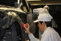 """塗装工程の途中、1台1台手作業による""""水研ぎ""""が施される。"""