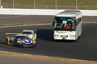 観光バスにからむ暴走族? 違います! サファリパークの猛獣見物のごとく、バスからスーパーGTのフリー走行を眺める「サーキットサファリ」。