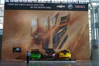 映画『トランスフォーマー4』の展示エリア。ロゴの描かれた壁の大きさときたら!手前に立つ警備員や展示車両が小さく見える。