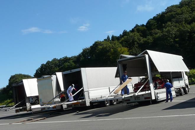 朝9時、走行テストの会場となるツインリンクもてぎの南コースに、Hondaコレクションホールの収蔵車両を積んだトラックが次々に到着。搬入が始まる。