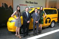 「日産NV200 ニューヨーク市タクシー」と、日産自動車の片桐隆夫副社長(中央左)、松屋 銀座本店の古屋毅彦取締役 店長。