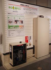 写真左のボックスがホンダの「家庭用ガスエンジンコージェネレーションユニット」。都市ガスやLPガスを燃料に発電、廃熱を利用して湯も沸かす。右はそのお湯をためる給湯ユニット。システムの総称が「エコウィルプラス」。