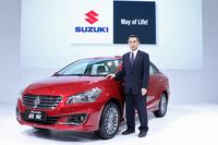 新型車「スズキ・アリビオ」とスズキの鈴木俊宏副社長。
