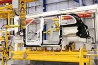 工場を流れる新型ロンドンタクシーのボディー。ボディーは総アルミ製で、組み立てに際しては溶接を使わず、すべて接着で行っている。