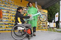 「エッフェル塔は東京タワーより高い。ウィかノンか?」という問題から始まった「ルノージャポン・ウルトラクイズ」の優勝者に、ゲストの青木琢磨氏から賞品のルノー・ブランドの折り畳み自転車が渡された。後ろのパネルに貼られた写真は、「カングー日本の道を行く」と題された来場者によるフォトコンテストの応募作品。