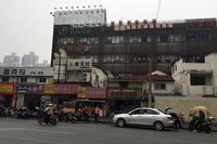 上海・中山公園付近で。高層アパートやオフィスが立ち並ぶそばに、古い商店や建物が残る。