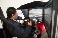 """ドライブシミュレーターのi-Racingも設置されていた。楽しげに体験しているのは""""バイパーほった""""氏ことwebCGの堀田編集部員。"""