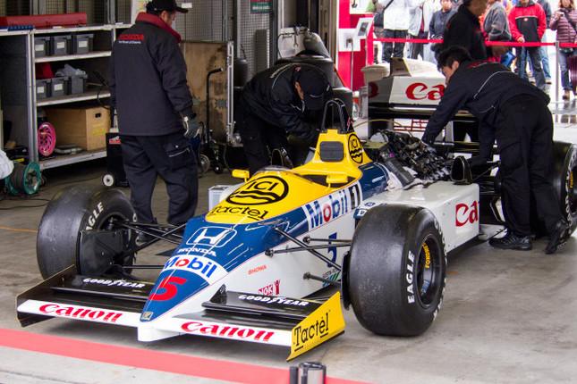 """二輪、四輪の新旧レーシングマシンがツインリンクもてぎに集結した。こちらは「ウィリアムズ・ホンダFW11」。1986年にナイジェル・マンセルがステアリングを握った""""レッドファイブ""""。"""