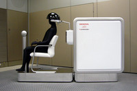 こちらが新開発の脳計測装置。写真左側の椅子に座ったオペレーターは、脳波と脳血流を計られることでアシモなどのロボットに指令を送る。総重量300kgのこの装置、手のひらサイズになるのはいつの日か。