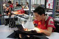 切り抜かれた革をミシンで縫製しているところ。