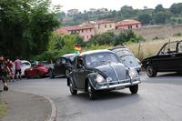 新車時からと思われる古いフィレンツェナンバーをもつ1963年「ビートル」が行く。後方にはドイツ・ヴォルクスブルクから駆けつけたビートルたちが。