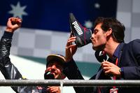 """フェラーリの2台と僚友フェルスタッペンのスタート直後の接触により前が開けたリカルド(左)は2戦連続の2位表彰台を獲得。おなじみになりつつあるドライビングシューズでシャンパンをいただく""""奇行""""を、インタビュアーとして登壇した母国オーストラリアの先輩、マーク・ウェバー(右)にもさせる暴挙(!?)に出た。ドライバーズチャンピオンシップで3位を守っている。(Photo=Red Bull Racing)"""