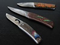 ペーパークラフトに専念する前は七宝焼きも手がけ、日本七宝作家協会の国際展で受賞したこともあった。写真はダマスカス鋼のフォールデングナイフのハンドルに七宝焼を取り入れ、デザインしたもの。