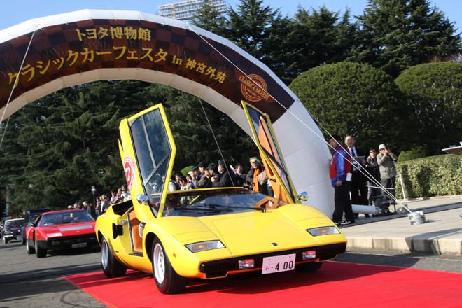 シザースドアをはね上げたお約束のスタイルで、レッドカーペットの敷かれた花道を進む1977年「ランボルギーニ・カウンタックLP400」。エントリー車両はカーペット上で一時停止し、オーナーと車両の紹介を受けてからパレードに向かう。