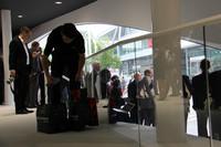 捨てられた報道資料のカバーなどを手提げ袋に集める清掃スタッフ。