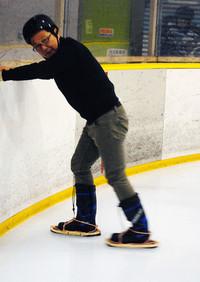 氷上で恐る恐る特製かんじきを試す筆者。ヘルメットに頭が入っていないのはご愛嬌(あいきょう)。