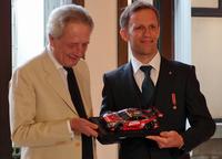 勲章のお返しに、クインタレッリ氏からジョルジ大使に、自身が駆るレーシングカーのミニチュアが贈られた。「子どものような、うれしい気持ちになりますね」と、大使もご満悦の様子。