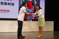 記者会見にて、Hondaウエルカムプラザ青山のスタッフから花束を渡される佐藤選手。