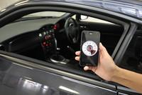 「写真奥に見える『86』のエンジン回転数を、スマートフォン上に表示する」デモの様子。ゆくゆくは水温などのデータまで採取・蓄積できるようにし、「ドライビング・アプリ」として活用することも検討されている。