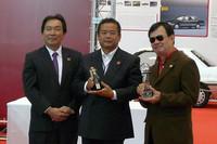 会場では日本カー・オブ・ザ・イヤーと同じく誕生30周年を迎える、タカラトミーの「チョロQ」に、選考委員特別賞が贈られた。中央はタカラトミーの佐藤慶太取締役副社長。
