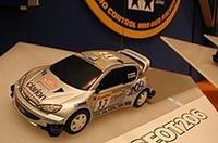 写真最上:最大面積を誇るタミヤのブースにおける、このショーでお披露目された「ラジ四駆」のコーナー。写真2番目:これが「ラジ四駆」のマシン。モデルはプジョー206WRCで、スケールは約1/28(全長154mm)。ほかにインプレッサWRC2002とランエボVII WRCの計3種が発表された。