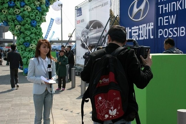 プレスデイ初日の朝、正門前でコメント撮りをするTVレポーター。見て分かるとおり、いたってまじめ。現地のTVクルーのマナーは日本より上だった。