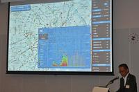 記者会見にて「ビッグデータ交通情報システム」について説明するトヨタ自動車の友山茂樹常務役員。スクリーンに映し出されているのが、新サービスを支える「G-BOOK」のプローブ情報だ。