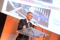 経営改革のスローガン「バック・イン・ザ・レース」のスライドを前にスピーチするPSAプジョー・シトロエンのカルロス・タバレスCEO。