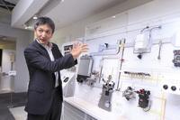 デンソー本社の技術展示スペースにて、コモンレールシステムの機構を説明するデンソーの竹内克彦氏。この機構を世界で初めて量産化したのも、実はデンソーなのだ。