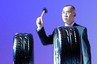 スポンジ入り、無しのタイヤをハンマーで叩き、音の発生を実演する、住友ゴム工業タイヤ技術本部の長谷川裕貢氏。