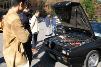「シャマル」のV8ツインターボエンジンを覗き込む参加者たち。赤い結晶塗装のヘッドを前に、話しているのはやはりあのこと?