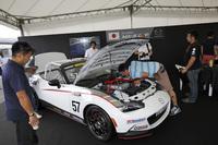 ワンメイクレースの参戦マシンを、来場者が興味深そうにチェックする。