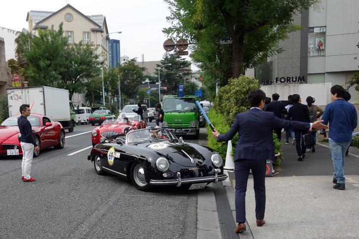 会場の入り口にて、参加車両の1954年式「ポルシェ356スピードスター」を誘導するオフィシャルのスタッフ。こうしたイベントを支える、縁の下の力持ちである。