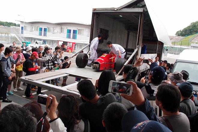 """さまざまなレーシングマシンが間近に見られるモータースポーツイベント「SUZUKA Sound of ENGINE 2015」。初開催の今回、特に注目すべき""""フィーチャリング・マシン""""に選ばれたのは、1987年のF1日本GP(鈴鹿では初開催)を制した「フェラーリF187」だった。写真は、そのF187がパドックに到着したときの光景。多くのファンが見守る中、ゆっくりとトランスポーターから下ろされた。"""