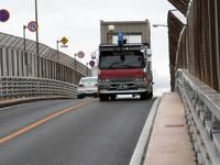 浦戸大橋で。狭い歩道だけにすがって進む歩行者のすぐ傍らを、ダンプがごう音を立てて駆け下りてくる。強風にあおられると本当に怖い。