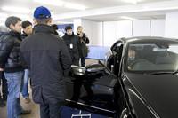 試乗前にドライビングポジションについて説明する、レーシングドライバーの松田晃司氏。