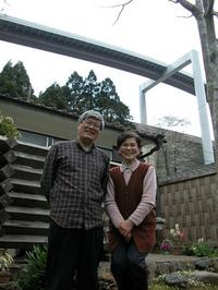 峰尾章子さんの自宅の前で、峰尾さん(右)と高尾山の自然を守る市民の会の事務局長、橋本良仁さん。背後には無機質な橋がつくられている。