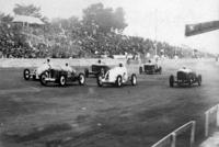 1937年5月に開かれた第3回全日本自動車競争大会における商工大臣杯(国産小型車によるレース)のスタートシーン。先頭集団は戦前にダットサンと覇を競ったオオタのワークスチーム。満員の観衆が座っているのは、今も残るコンクリートのグランドスタンドである。
