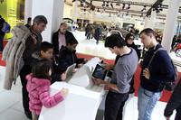 フォルクスワーゲンのシミュレーションゲームを、用意されたiPadで楽しむ来場者たち。2010年12月、ボローニャモーターショーで。