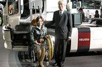 いすゞ自動車の井田義則社長(右)の後ろには、トラックの福祉車両「ギガマックストラクタAC(アクティブキャブ)」。リモコンでドアを開け、リフトに車椅子を固定、上がりきったら90度回転し乗車完了となる。