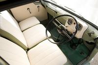 シンプルなインテリア。シートや内張りはオリジナルに近い色目のビニールレザーで張り替えられ、失われていたドアハンドルやキーは残されていた図面に従って複製された。エンジン本体はもちろん、ラジエターなどの補機類もシート下に収めているため足元は広々としている。4段ギアボックスのシフトレバーはコラムにある。