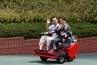 昭和40年代に人気を博したという「走るイス」の復刻版もパレードに参加。ハンドルを握るのは多摩テック所長、浴衣姿は園内にある天然温泉「クア・ガーデン」の女将。