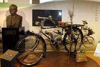 スズキの自動車業界における処女作であるバイクモーター「パワーフリーE2」(1952年)。36ccの空冷2ストローク単気筒、最高出力1.0ps/4000rpm。左の胸像は2代目社長の鈴木俊三。