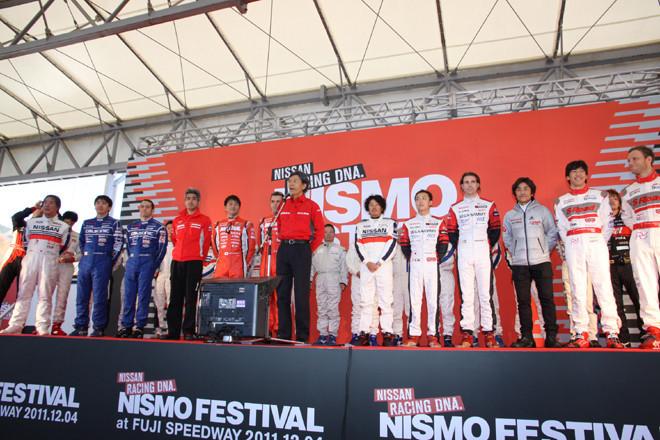 グランドスタンド裏のイベントエリアに設けられたステージに、全出場ドライバーとチーム監督が顔をそろえた「オープニング」で、開会を告げるNISMOの柿本邦彦総監督。この後、ドライバーを代表して本山哲選手があいさつした。