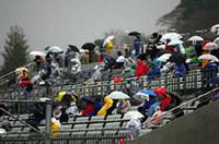 降りしきる冷たい雨の中、視線は、スタートラインに釘付け。レースのスタートを「いまかいまか」と待ちつづけた、1コーナー指定席の観客たち。