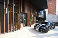「オートバックス代官山店」のカフェ&ギャラリースペース「ポディウムカフェ」と、記者の「ダッジ・バイパー」。展示は2月19日まで……だったのだけど、好評につき(?)24日までに延長されました! 興味のある人はぜひ。