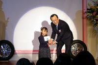 鈴木愛渚ちゃんは4歳。おばあちゃんの干し柿を題材にしての受賞だ。右は、ブリヂストン社長の荒川詔四氏。