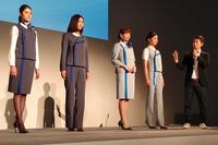 発表会場でのひとこま。デザイナーの江角泰俊氏(写真右端)が自ら、春夏用(右側の2着)と秋冬用(左側の2着)それぞれのポイントを解説した。