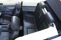 大人用として実用的な空間を確保したリアシート。ただし、直立に近いバックレストと、足先を向こうずね下部あたりまで前席下に入れることで、ヒザ前空間を稼ぐ。