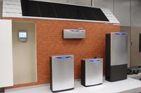 会場には、(写真右から)給湯ユニット、発電ユニットなど「ホンダ・スマート・ホーム・システム」を構成するアイテムが勢ぞろい。ユーザーは、一番左(室内)に見えるモニターでエネルギーの使用状況を確認できる。各ユニットのサイズは小さくなる傾向にあり、狭小住宅への設置対応も進められる。